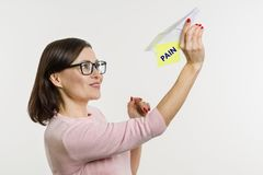 La donna si libera del dolore Invia l'aeroplano astratto di carta con il dolore di parola fotografia stock