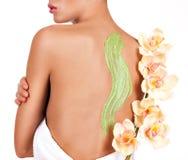 La donna si preoccupa per pelle del corpo che usando il cosmetico sfrega sulla parte posteriore Immagine Stock Libera da Diritti