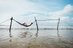 La donna si rilassa la menzogne nell'oscillazione dell'amaca sopra la linea della spuma dell'oceano Fotografie Stock