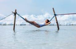 La donna si rilassa la menzogne nell'oscillazione dell'amaca sopra la linea della spuma dell'oceano Fotografia Stock