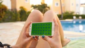 La donna si rilassa su sunbath nella piscina con per mezzo del telefono cellulare archivi video