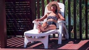 La donna si rilassa su una chaise-lounge archivi video