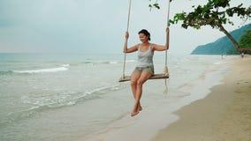 La donna si rilassa sull'oscillazione alla spiaggia stock footage