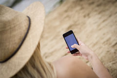 La donna si è seduta sulla spiaggia facendo uso di un telefono cellulare Fotografie Stock Libere da Diritti