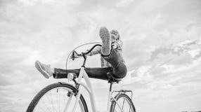 La donna si sente libero mentre goda di di ciclare La ragazza guida il fondo del cielo della bicicletta Il riciclaggio vi dà la s immagini stock