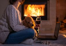 La donna si siede al pavimento con un computer portatile e un vino bevente sui precedenti del camino fotografie stock libere da diritti