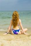 La donna si siede in bikini dal mare Fotografia Stock