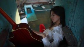 La donna si siede con la chitarra dentro di vecchia nave stock footage