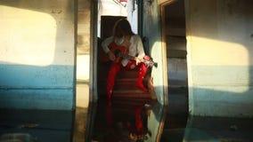 La donna si siede e gioca la chitarra dentro di vecchia nave stock footage