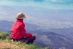 La donna si siede e guardando lontano alle montagne Immagine Stock