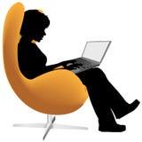 La donna si siede il lavoro della presidenza sul computer portatile Immagine Stock