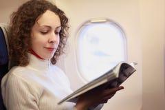 La donna si siede in lampadina di nea della presidenza dell'aeroplano Fotografie Stock Libere da Diritti