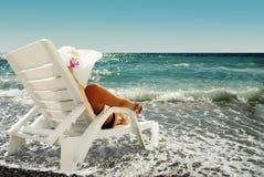 La donna si siede nel salotto del chaise sulla spiaggia del mare Fotografia Stock