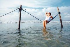 La donna si siede nell'oscillazione dell'amaca sopra la linea della spuma dell'oceano - l'estate dell'isola Fotografie Stock Libere da Diritti