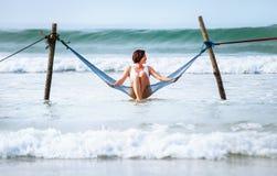 La donna si siede nell'oscillazione dell'amaca sopra la linea della spuma dell'oceano - l'estate dell'isola Fotografia Stock Libera da Diritti
