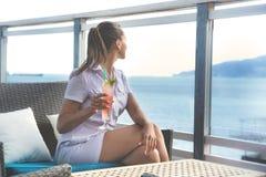 La donna si siede nella barra della spiaggia con coctail fotografia stock