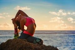 La donna si siede nella posa di yoga sulla spiaggia del mare del tramonto Immagine Stock