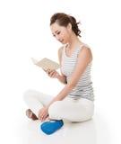 La donna si siede su terra ed ha letto un libro fotografie stock libere da diritti
