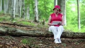 La donna si siede su un albero caduto nella foresta ed utilizza il PC della compressa video d archivio