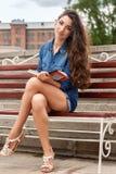 La donna si siede su un banco e legge il libro Immagine Stock