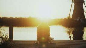 La donna si siede su un pilastro del piccolo lago, guardante il tramonto Ora dorata Momento perfetto di pace e di armonia interna stock footage