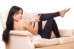 La donna si siede sul sofà Fotografia Stock Libera da Diritti