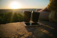 La donna si siede sulla collina con le tazze del cofee Fotografia Stock Libera da Diritti