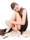 La donna si siede sulla pelle lanuginosa molle delle pecore Immagini Stock
