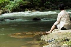 La donna si siede sulla roccia vicino alla cascata, fiume, rapido fotografie stock