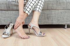 La donna si siede sulla sedia e la mano femminile con dolore del piede dopo, prende SH Immagine Stock Libera da Diritti