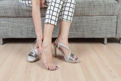 La donna si siede sulla sedia e la mano femminile con dolore del piede dopo, prende SH Fotografia Stock Libera da Diritti