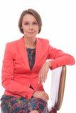 La donna si siede sulla sedia isolata con bianco immagine stock