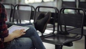La donna si siede sulla sedia nera in aeroporto e sui giochi con il touchpad stock footage