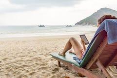 La donna si siede in un lettino su una spiaggia tropicale e legge un E-lettore Fotografie Stock Libere da Diritti