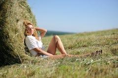 La donna si siede vicino al mucchio di fieno Fotografie Stock Libere da Diritti