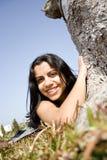 La donna si trova su un'erba e sul contatto dell'albero Immagini Stock