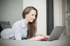 La donna si trova sul letto con un computer portatile Fotografia Stock Libera da Diritti