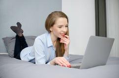 La donna si trova sul letto con un computer portatile Fotografie Stock Libere da Diritti