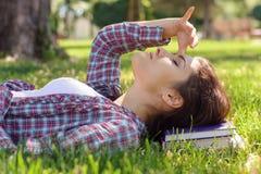 La donna si trova sull'erba nel parco Fotografia Stock Libera da Diritti