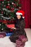 La donna sistema i regali di natale vicino all'albero Fotografie Stock Libere da Diritti