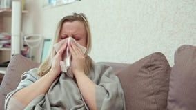La donna soffia il suo naso in un fazzoletto di carta Ha il raffreddore, emicrania video d archivio