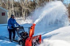 La donna soffia la neve dopo la tempesta Fotografie Stock