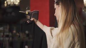 La donna sola è in un negozio di progettazione con i vestiti, esaminanti l'indumento sul gancio archivi video
