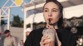 La donna sola sta bevendo il caffè, tenente la tazza in mani all'aperto nella sera dell'estate stock footage