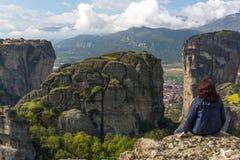 La donna sola sta sedendosi su nelle montagne gode della vista Fotografia Stock Libera da Diritti