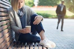 La donna sola sta sedendosi sul banco e sta tenendo il caffè Fotografia Stock Libera da Diritti