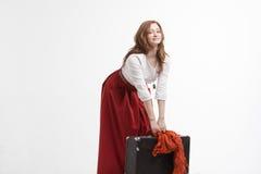 La donna solleva una valigia pesante fotografia stock