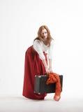 La donna solleva una valigia pesante Fotografie Stock Libere da Diritti