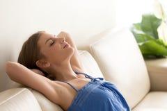 La donna sonnecchia sullo strato con le mani dietro la testa Immagini Stock
