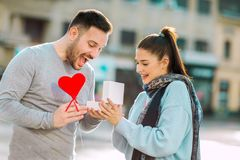 La donna sorprende l'uomo con un regalo Fotografia Stock Libera da Diritti